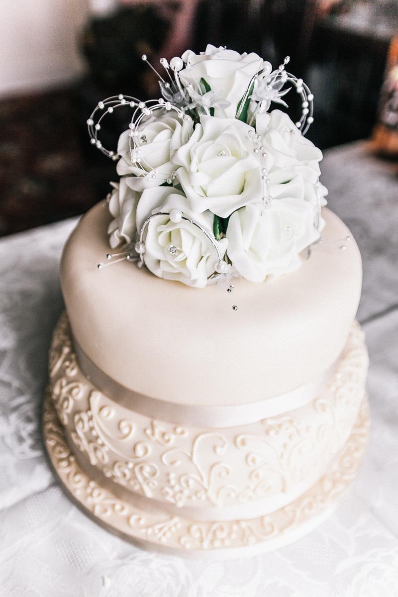 golden cream wedding cake with white roses